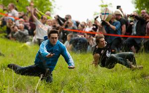 FIXATION YOUNG PHOTOGRAPHY BURSARY FINALIST Competitors compete in the annual Cheese Rolling event on Coopers Hill, Gloucestershire, England. May 26 2014. The event sees competitors race a round cheese down the steep slope, with the first person to the bottom being the winner. Picture: Alastair Johnstone