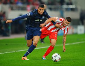PIRAEUS, GREECE - FEBRUARY 25:  Chris Smalling (L) of Manchester United holds off the challenge of Hernan Perez (R) of Olympiacos during the UEFA Champions League Round of 16 first leg match between Olympiacos FC and Manchester United at Karaiskakis Stadium on February 25, 2014 in Piraeus, Greece.  (Photo by Michael Regan/Getty Images)