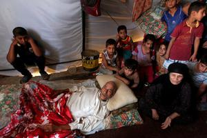 An Iraqi family, who fled the city of Ramadi after it was seized by Islamic State (IS) group militants, gathers inside a tent at a camp housing displaced families on May 18, 2015 in Bzeibez, on the southwestern frontier of Baghdad with Anbar province. Shiite militias converged on Ramadi in a bid to recapture it from jihadists who dealt the Iraqi government a stinging blow by overrunning the city in a deadly three-day blitz. AFP PHOTO / AHMAD AL-RUBAYEAHMAD AL-RUBAYE/AFP/Getty Images