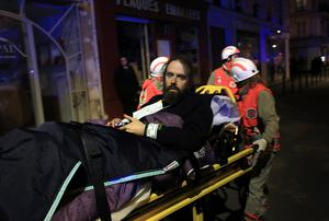 A man is being evacuated from the Bataclan theater after a shooting in Paris, Friday Nov. 13, 2015.  French President Francois Hollande declared a state of emergency and announced that he was closing the country's borders. (AP Photo/Thibault Camus)