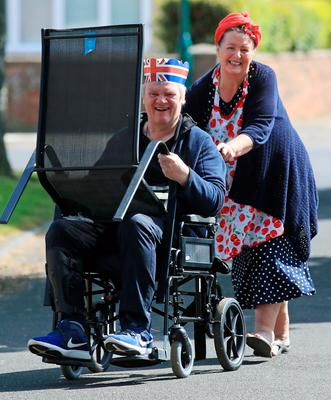 A man and a woman move a chair ahead of their street's celebrations in Duncan Avenue, Redcar, to mark the 75th anniversary of VE Day. PA Photo. Picture date: Friday May 8, 2020. See PA story MEMORIAL VE . Photo credit should read: Owen Humphreys/PA Wire