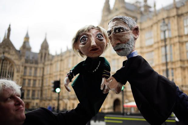 Two anti-Brexit activists pose with their hand-puppets depicting British Prime Minister and leader of the Conservative party Theresa May, left, and Britain's Labour party leader Jeremy Corbyn, in front of the the Houses of Parliament on election day in London, Thursday, June 8, 2017. (AP Photo/Markus Schreiber)