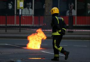 Flames are seen escaping from a manhole cover as fire crews tend to an underground cable fire at Lincoln's Inn Fields in on April 1, 2015 in London, England.  (Photo by Dan Kitwood/Getty Images)