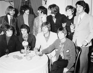 "From left to right: George Alexander; Pete Swettenham, Geoffrey Swettenham and John Perry, the four members of the ""Grapefruit"" pop group are seen seated at a table at the launch of their record ""Dear Delilah, in the Mayfair Suite at Hanover Grand Hotel in London in 1968, with with Brian Jones of the Rolling Stones, folk singer Donovan; Beatles' Ringo Starr and John Lennon; Cilla Black and Paul McCartney in the background. (AP Photo/Robert Dear, File)"
