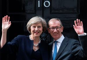 Britain's new Prime Minister Theresa May (L) and her husband Philip John (R) wave outside 10 Downing Street in central London on July 13, 2016 on the day she takes office following the formal resignation of David Cameron. AFP/Getty Images