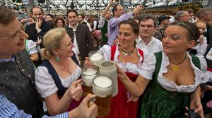 "MUNICH, GERMANY - SEPTEMBER 21:  Visitors in bavarian style clothes raise their glasses after getting their first Oktoberfest-beer in the Schottenhamel-tent at the Oktoberfest 2013 beer festival at Theresienwiese on September 21, 2013 in Munich, Germany. Shortly before Munich mayor Christian Ude (SPD) had tapped the first barrel with the traditional ""O'zapft is!"" (""It's tapped!"") to launch the festival. The Munich Oktoberfest, which this year will run from September 21 through October 6, is the world's largest beer fest and draws millions of visitors. (Photo by Joerg Koch/Getty Images)"