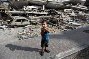 Palestinian Abdel Aziz Jendiyah, 4, stands in front of a six-story building, destroyed by an Israeli strike, adjacent to his family house, in the Sabra neighborhood of Gaza City, northern Gaza Strip, Thursday, July 31, 2014. (AP Photo/Lefteris Pitarakis)