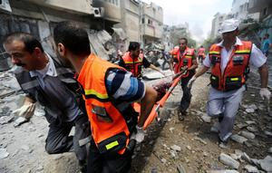 Palestinian medics carry a man injured in Gaza City's Shijaiyah neighborhood that came under fire as Israel widened its ground offensive against Hamas in the northern Gaza Strip on Sunday, July 20, 2014.  (AP Photo/Hatem Moussa)