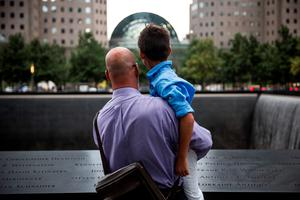 NEW YORK, NY - SEPTEMBER 11:  Paul Bloess, of Levittown, NY, holds his son, Maxavater Bloess, age 10, in a moment of silence at the 9-11 memorial site on September 11, 2015 in New York City. Today marks the 14th anniversary of the attacks where nearly 3,000 people were killed in New York, Washington D.C. and Pennsylvania.  (Photo by Andrew Burton/Getty Images)