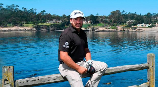Water view: Graeme McDowell on the 18th tee at Pebble Beach yesterday