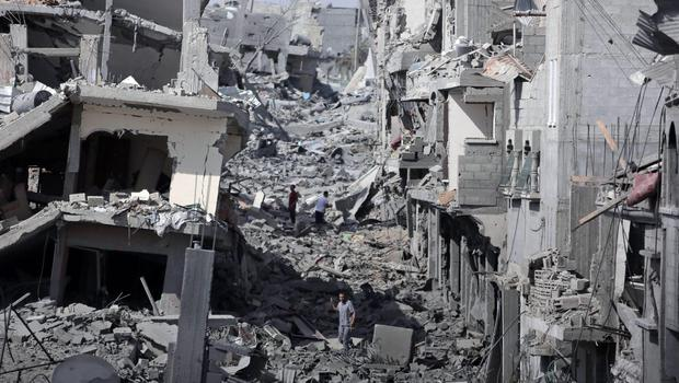 Palestinians inspect the damage of their destroyed houses during a 12-hour cease-fire in Gaza City's Shijaiyah neighborhood, Saturday, July 26, 2014. (AP Photo/Khalil Hamra)