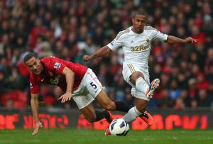 MANCHESTER, ENGLAND - MAY 12:  Wayne Routledge of Swansea City tangles with Rio Ferdinand of Manchester United during the Barclays Premier League match between Manchester United and Swansea City at Old Trafford on May 12, 2013 in Manchester, England.  (Photo by Alex Livesey/Getty Images)