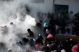 Policemen try to disperse hundreds of migrants by spraying them with fire extinguishers during a gathering for a registration procedure at the stadium on the Greek island of Kos, on August 11, 2015. Police on the Greek island on Kos hit migrants with truncheons to prevent a stampede, a day after an officer was caught on camera slapping a migrant. The incident occurred as hundreds of migrants were being relocated to a local football stadium, after camping alongside roads and beaches across the island for weeks. AFP PHOTO / ANGELOS TZORTZINISANGELOS TZORTZINIS/AFP/Getty Images