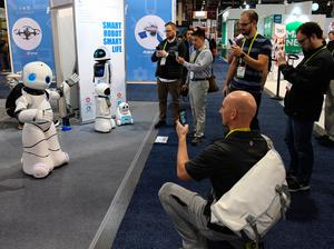 LAS VEGAS, NV - JANUARY 05:  Attendees watch a Tanscorp UU smart robot dance to a Michael Jackson song it is playing at CES 2017 at the Sands Expo and Convention Center on January 5, 2017 in Las Vegas, Nevada. CES, the world's largest annual consumer technology trade show, runs through January 8 and features 3,800 exhibitors showing off their latest products and services to more than 165,000 attendees.  (Photo by Ethan Miller/Getty Images)