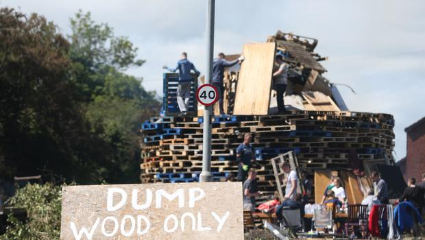 The scene on Love Lane in Carrickfergus as the local community rebuild a bonfire after the original bonfire they build was burnt on Monday evening.  Picture by Matt Mackey / presseye.com 10/07/2017