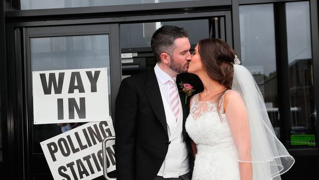 Alliance candidate for West Belfast Sorcha Eastwood casts her vote in the 2017 General Election, with her husband, Dale Shirlow, at a polling station in Lisburn, Northern Ireland, still wearing her wedding dress after they were married earlier in the day. PRESS ASSOCIATION Photo. Picture date: Thursday June 8, 2017. See PA story ELECTION Main. Photo credit should read: Brian Lawless/PA Wire