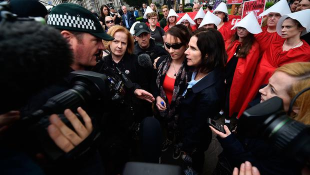 Doctor Rebecca Gomparts (R) comforts a woman after she is is led away by a police officer for questioning after taking an abortion pill as abortion rights campaign group ROSA, Reproductive Rights Against Oppression, Sexism and Austerity distribute abortion pills from a touring bus on May 31, 2018 in Belfast, Northern Ireland. (Photo by Charles McQuillan/Getty Images)