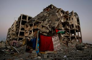 A makeshift tent stands near to the destruction of buildings at a residential neighborhood, in Beit Lahiya, northern Gaza Strip, Thursday, Aug. 7, 2014.  (AP Photo/Hatem Moussa)