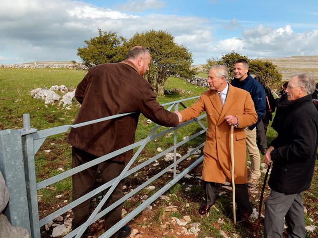 THE BURREN, IRELAND - MAY 19:  Prince Charles, Prince of Wales shakes hands with local farmer Oliver Nagle with his father Pat (R) looking on during his visit to The Burren, an ancient and dramatic stony outcrop famed for its rare plant life, biodiversity and archaeology, on the first day of his Royal visit to the Republic of Ireland on May 19, 2015 in County Clare, Ireland. The Prince of Wales and Duchess of Cornwall arrived in Ireland today for their four day visit to the Republic and Northern Ireland, the visit has been described by the British Embassy as another important step in promoting peace and reconciliation. (Photo by John Stillwell - WPA Pool/Getty Images)