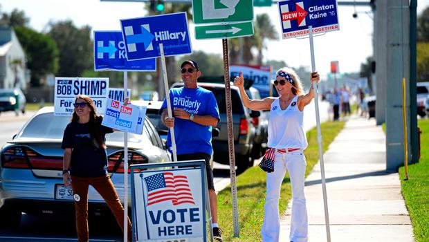 A group of volunteers for Hillary Clinton, from left, Kelley Layton, Steve Haerter, and Joyce DeVane wave to passing traffic on 3rd Street in Neptune Beach, Fla., Tuesday, Nov. 8, 2016, near the polling place at the Beaches Branch of the Jacksonville Public Library.  (Bob Mack/The Florida Times-Union via AP)
