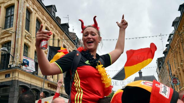 A Belgium's supporter wearing devil's horns celebrates as she gathers with other supporters in the main square, La Grand Place, in Lille on July 1, 2016 ahead of the Euro 2016 football tournament quarter final match between Belgium and Wales. / AFP PHOTO / PHILIPPE HUGUENPHILIPPE HUGUEN/AFP/Getty Images