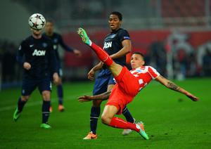 PIRAEUS, GREECE - FEBRUARY 25:  Jose Holebas (R) of Olympiacos clears the ball ahead of Antonio Valencia (L) of Manchester United during the UEFA Champions League Round of 16 first leg match between Olympiacos FC and Manchester United at Karaiskakis Stadium on February 25, 2014 in Piraeus, Greece.  (Photo by Michael Regan/Getty Images)