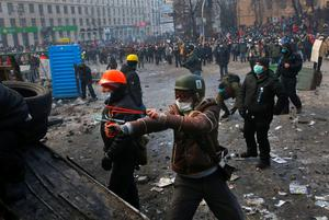 Protesters clash with police, in central Kiev, Ukraine, Monday, Jan. 20, 2014. Protesters erected barricades from charred vehicles and other materials in central Kiev as the sound of stun grenades can be heard in the freezing air as police try to quell anti-government street protests. (AP Photo/Sergei Grits)