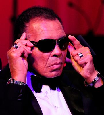 This file photo taken on March 24, 2012 shows Boxing legend Muhammad Ali adjusting his glasses on stage at Muhammad Ali's Celebrity Fight Night XVIII in Phoenix, Arizona.  Boxing legend Muhammad Ali, dies at 74. The former heavyweight world champion was hospitalized on Thursday at a Phoenix, Arizona, hospital with a respiratory issue, which US media reported was complicated by his Parkinson's disease.  / AFP PHOTO / ROBYN BECKROBYN BECK/AFP/Getty Images