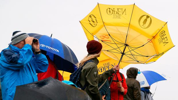 A spectator tries to adjust their umbrella during preview day four of The Open Championship 2019 at Royal Portrush Golf Club (Richard Sellers/PA)