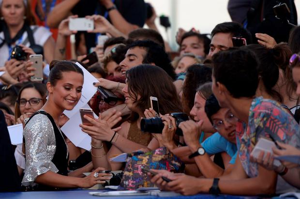 "Swedish actress Alicia Vikander poses with fans before the premiere of the movie ""The Light Between Oceans"" presented in competition at the 73rd Venice Film Festival on September 1, 2016 at Venice Lido. / AFP PHOTO / FILIPPO MONTEFORTEFILIPPO MONTEFORTE/AFP/Getty Images"
