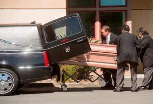 Funeral directors transport the body of an Irish student who died Tuesday when a Berkeley apartment balcony collapsed on Friday, June 19, 2015, in Oakland Calif. Caskets bearing four of the six victims arrived at St. Columba Catholic Church for a vigil Friday afternoon. (AP Photo/Noah Berger)