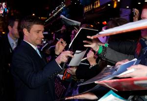 Martin Freeman signs autographs as he arrives on the green carpet for the premiere of The Hobbit: Battle of the Five Armies, at the Odeon Leicester Square in central London.