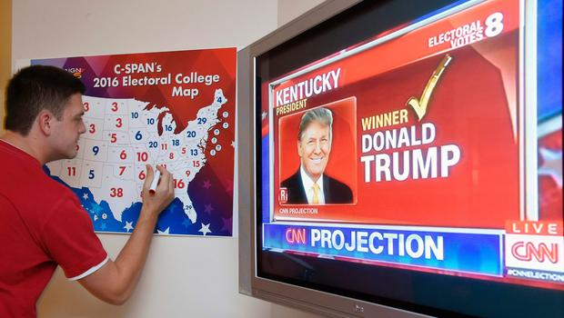 TOPSHOT - Jake Krupa colors in an electoral map as states are projected for Republican presidential candidate Donald Trump or Democratic Presidential candidate Hillary Clinton at an election watching party in Coconut Grove, Florida, on November 8, 2016.  / AFP PHOTO / RHONA WISERHONA WISE/AFP/Getty Images