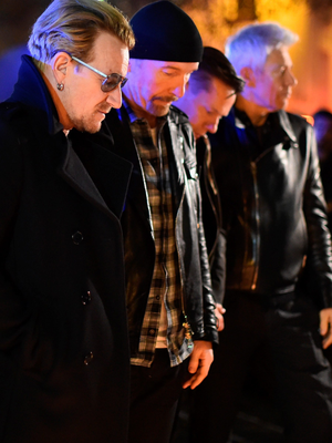 Bono and band members of U2 pay their respects and place flowers on the pavement near the scene of the Bataclan Theatre terrorist attack. (Photo by Jeff J Mitchell/Getty Images)