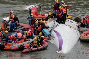 Emergency personnel try to extract passengers from a commercial plane after it crashed in Taipei, Taiwan, Wednesday, Feb. 4, 2015. The Taiwanese commercial flight with 58 people aboard clipped a bridge shortly after takeoff and crashed into a river in the island's capital of Taipei on Wednesday morning.  (AP Photo/Wally Santana)