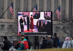 Supporters of US President-elect Donald Trump  watch a TV screen at the National Mall, as he arrives at the White House to greet US President Barack Obama in Washington, DC, on January 20, 2017. Donald Trump will be sworn in as the 45th president of the United States Friday -- winning vindication for his bare-knuckle White House bid and beginning a four-year term that promises to shake up Washington and the world. / AFP PHOTO / Andrew CABALLERO-REYNOLDSANDREW CABALLERO-REYNOLDS/AFP/Getty Images