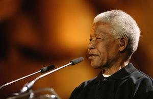 """CAPE TOWN, SOUTH AFRICA - NOVEMBER 29:  Nelson Mandela makes a speech at the """"46664 - Give One Minute of Your Life to AIDS"""" concert at Greenpoint Stadium on November 29, 2003 in Cape Town, South Africa. The concert will benefit the Nelson Mandela Foundation and the fight against AIDS in Africa.   (Photo by Getty Images)"""