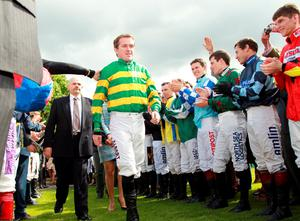 Northern Irish jockey Tony McCoy is cheered on by other jockeys as he arrives to be presented with the jockey championship cup on his retirement at Sandown Park Racecourse in Esher, Southern England, on April 25, 2015. Tony McCoy brings the curtain down on his record-breaking career on the aptly-named Box Office in front of a forecast full house at Sandown today. AFP PHOTO / SEAN DEMPSEYSEAN DEMPSEY/AFP/Getty Images