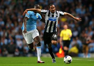 MANCHESTER, ENGLAND - AUGUST 19:  Jonas Gutierrez of Newcastle United holds off a challenge from Yaya Toure of Manchester City during the Barclays Premier League match between Manchester City and Newcastle United at the Etihad Stadium on August 19, 2013 in Manchester, England.  (Photo by Alex Livesey/Getty Images)