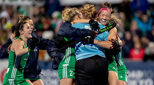 Irish players rush to celebrate with goalkeeper Ayeisha McFerran after she makes the save that sends them to the 2020 Tokyo Olympics