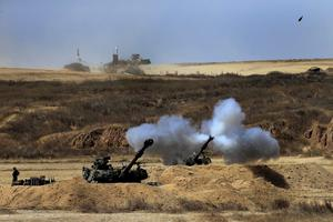 An Israeli tank fires towards Gaza, near the Israel and Gaza border in the morning of Sunday, July 27, 2014.  (AP Photo/Tsafrir Abayov)