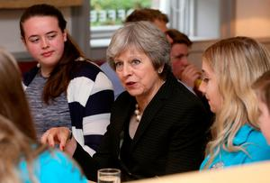 BELFAST, NORTHERN IRELAND - JULY 20: Britain's Prime Minister Theresa May (C) talks with people from the Belfast Youth Forum during her visit to the Crescent Arts Centre on July 20, 2018 in Belfast, Northern Ireland. With a trip to Northern Ireland this week, May began a tour of Britain to convince voters to back her blueprint for close economic ties with the bloc after Brexit next March. (Photo by Paul Faith - WPA Pool/Getty Images)