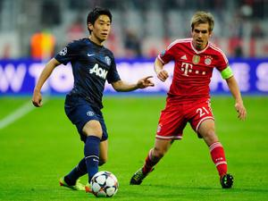 MUNICH, GERMANY - APRIL 09:  Philipp Lahm (R) of Muenchen challenges Shinji Kagawa of Manchester during the UEFA Champions League quarter-final second leg match between FC Bayern Muenchen and Manchester United at Allianz Arena on April 9, 2014 in Munich, Germany.  (Photo by Lennart Preiss/Bongarts/Getty Images)