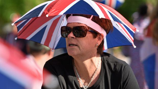 Under cover: A royal fan shelters under a Union flag parasol on the Long Walk in Windsor (David Mirzoeff/PA)