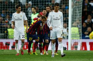 Lionel Messi of Barcelona celebrates scoring his team's third goal with team mates as Cristiano Ronaldo of Real Madrid look dejected during the La Liga match between Real Madrid CF and FC Barcelona at the Bernabeu on March 23, 2014 in Madrid, Spain.  (Photo by Gonzalo Arroyo Moreno/Getty Images)