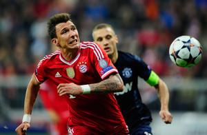 MUNICH, GERMANY - APRIL 09:  Mario Mandzukic (L) of Muenchen challenges Nemanja Vidic of Manchester during the UEFA Champions League quarter-final second leg match between FC Bayern Muenchen and Manchester United at Allianz Arena on April 9, 2014 in Munich, Germany.  (Photo by Lennart Preiss/Bongarts/Getty Images)