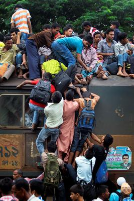 Bangladeshi Muslims try to climb up to the roof of a train to head home ahead of Eid al-Fitr as others wait at a railway station in Dhaka, Bangladesh, Thursday, Aug. 8, 2013. Hundreds of thousands of people working in Dhaka to make a living return home to spend time with their family during Eid al-Fitr. (AP Photo/A.M. Ahad)
