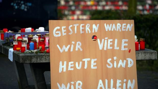 """A poster reading """"Yesterday we were many, today we are alone"""" can be seen in front of a memorial of flowers and candles near the Joseph-Koenig-Gymnasium secondary school in Haltern am See, western Germany on March 25, 2015, from where some of the Germanwings plane crash victims came. AFP PHOTO / SASCHA SCHUERMANNSASCHA SCHUERMANN/AFP/Getty Images"""