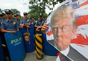 Protesters display a photo of U.S. President-elect Donald Trump during an anti-U.S. protest outside the US Embassy in Manila, Philippines Thursday, Nov. 10, 2016 in Manila, Philippines. Trump will become the 45th U.S. President after defeating Democratic presidential candidate Hillary Clinton in the Nov. 8, 2016 US election. (AP Photo/Bullit Marquez)