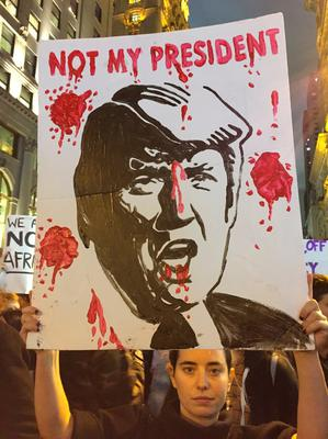 """Anna Ceraulo-Jalazo holds up a protest poster outside Trump Tower in New York as as thousands of protesters chanting """"not my president"""" blocked the city's Fifth Avenue in the aftermath of the US presidential elections. PRESS ASSOCIATION Photo. Picture date: Wednesday November 9, 2016. See PA story POLITICS President. Photo credit should read: David Mercer/PA Wire"""